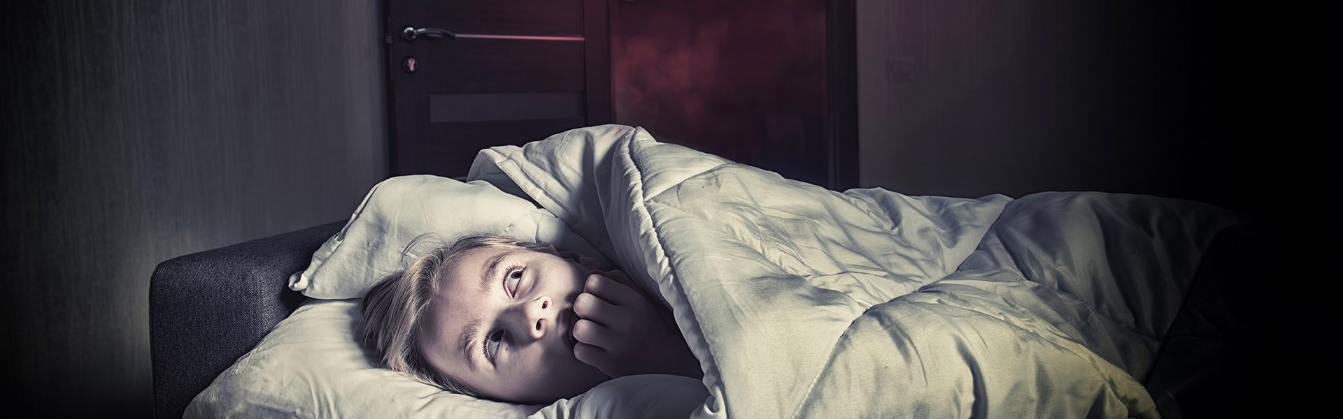 kids hiding under the covers in a dark bedroom